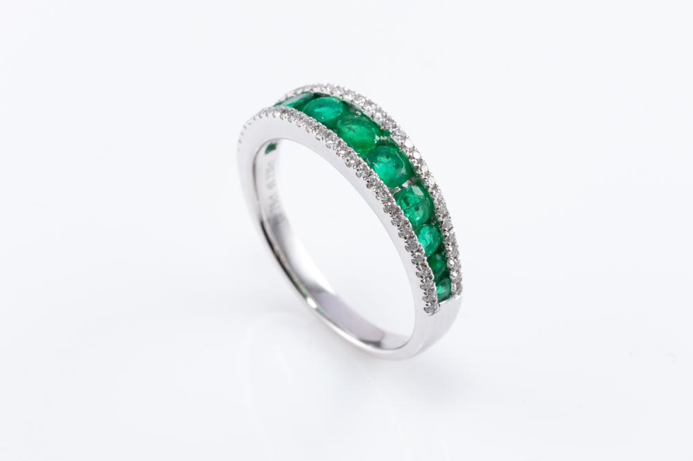 A HALF HOOP EMERALD AND DIAMOND RING; channel set with 11 graduated round cut emeralds between 58 round brilliant cut diamonds total...