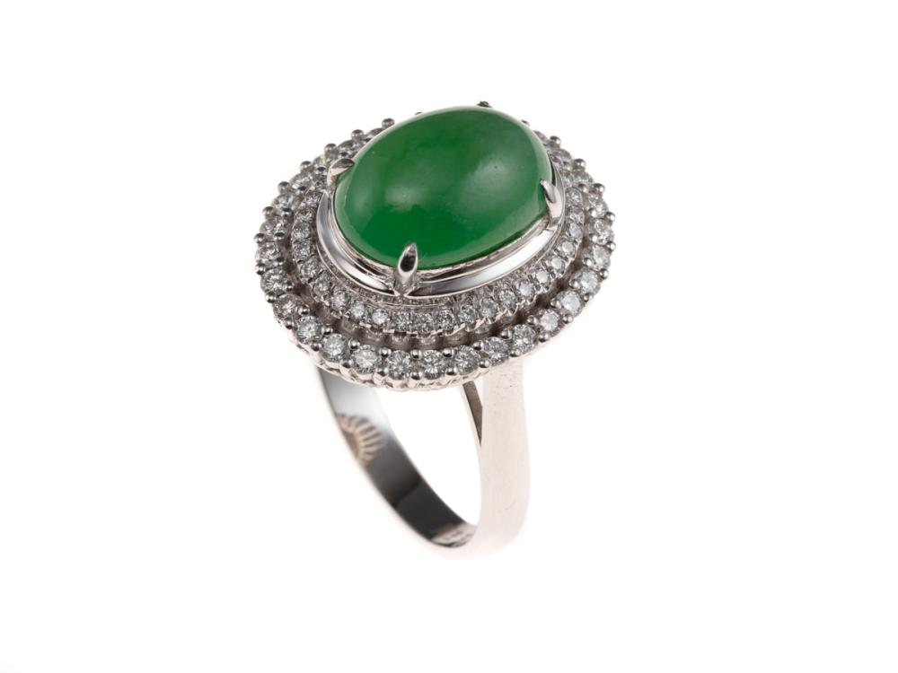 AN 18CT WHITE GOLD JADE AND DIAMOND RING; centring on a 12 x 8.6mm fine green cabochon jadeite jade surmounting a 2 tiered border on...