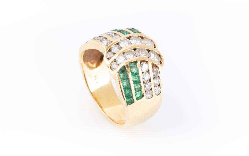 AN 18CT GOLD EMERALD AND DIAMOND RING; wave form channel set with 16 mixed cut emeralds and 25 round brilliant cut diamonds, size M,...