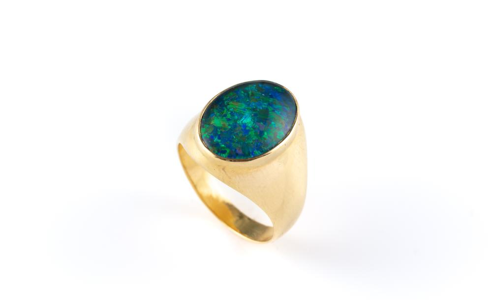 A GENTS 18CT GOLD OPAL RING; tapering shank set with an opal triplet, size R, wt. 12.58g.