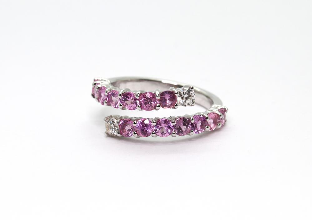A PINK SAPPHIRE AND DIAMOND RING; 18ct white gold bypass ring set with 14 round cut pink sapphires and 2 round brilliant cut diamond...