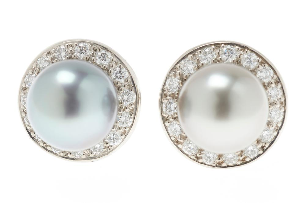 A PAIR OF TAHITIAN PEARL AND DIAMOND STUD EARRINGS; each a 9.5mm round cultured pearl of fine colour and lustre set above a circle o...