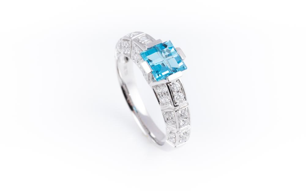 AN 18CT WHITE GOLD TOPAZ AND DIAMOND RING; geometric design invisible set with 4 carre cut blue topaz above gallery and shank half h...
