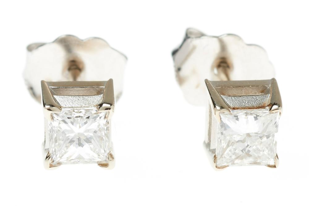 A PAIR OF 18CT WHITE GOLD SOLITAIRE DIAMOND STUD EARRINGS; each set with a princess cut diamond, the two totalling 0.45ct, F/VS.