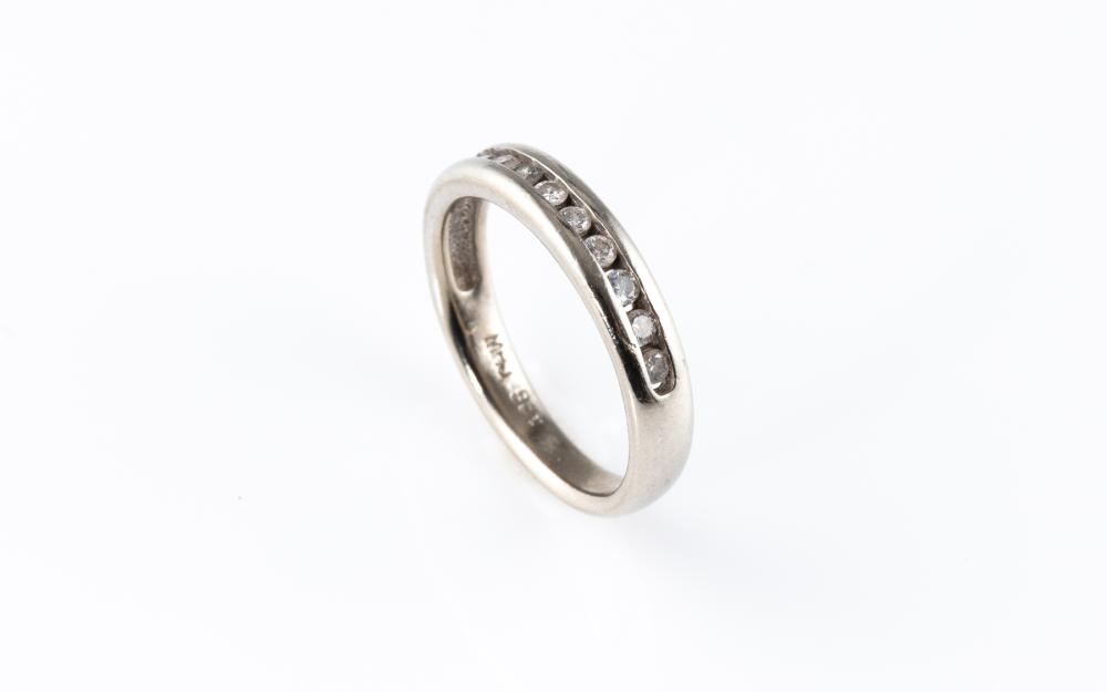 A 9CT WHITE GOLD DIAMOND RING; half hoop channel set with 10 round brilliant cut diamonds, size M, wt. 3g.