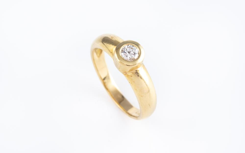 AN 18CT GOLD SOLITAIRE DIAMOND RING; bezel set with a round brilliant cut diamond of approx. 0.20ct, P1, size M 1/2, wt. 4.28g.