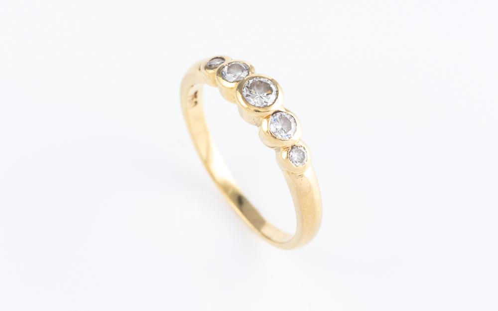 AN 18CT GOLD DIAMOND RING; rub set across the top with 5 graduated round brilliant cut diamonds, totalling approx. 0.21ct, size K1/2.