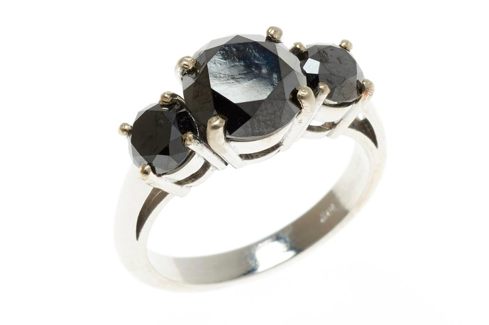 A 14CT WHITE GOLD THREE STONE BLACK DIAMOND RING; beaded claw set with 3 round brilliant cut black diamonds totalling approx. 3.63ct...