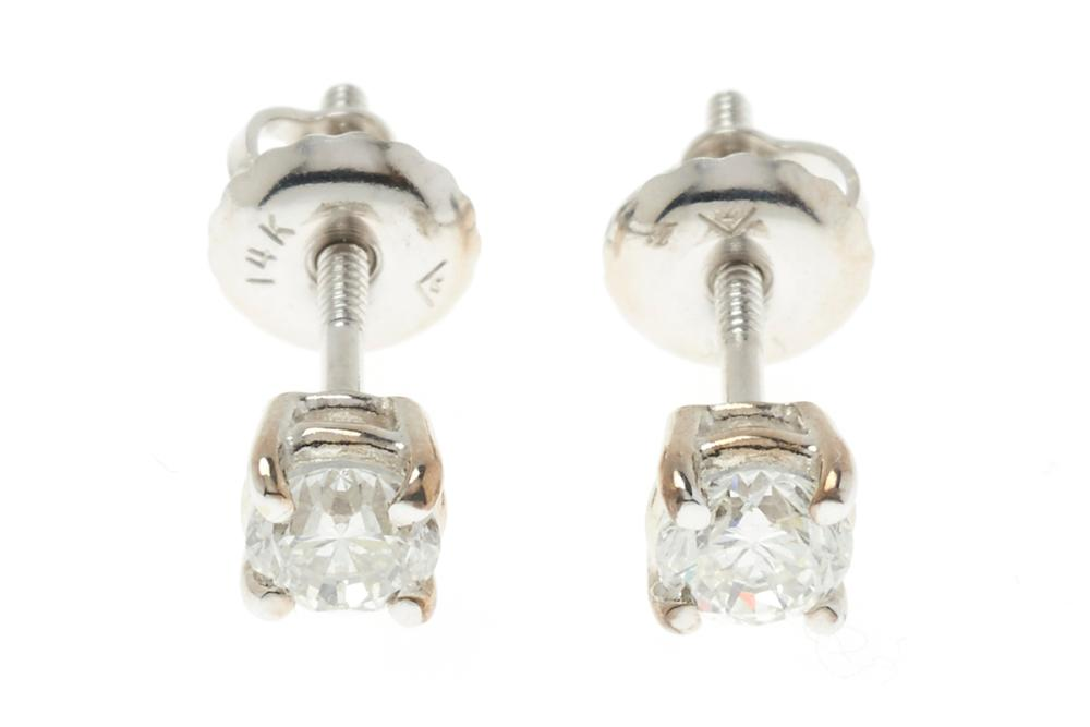 A PAIR OF 18CT WHITE GOLD SOLITAIRE DIAMOND STUD EARRINGS; each set with a round brilliant cut diamond of 0.25ct G/SI, on threaded p..