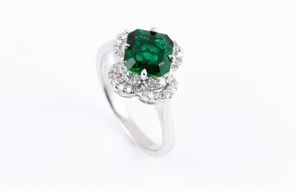 AN 18CT WHITE GOLD TOURMALINE AND DIAMOND RING; featuring a step cut fine green chrome tourmaline of approx. 1.7ct, above quatrefoil...