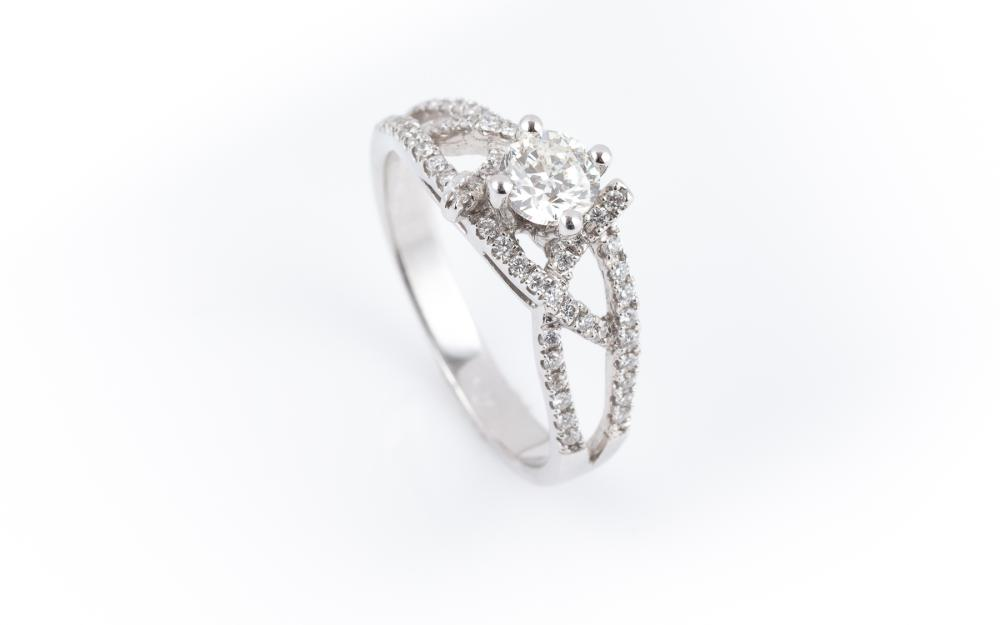 AN 18CT WHITE GOLD DIAMOND RING; four bead claw set with a round brilliant cut diamond of approx. 0.40ct SI2, to split cross over sh...