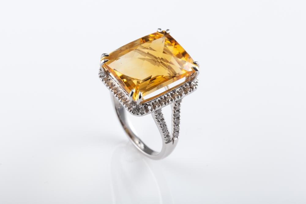 AN 18CT WHITE GOLD CITRINE AND DIAMOND COCKTAIL RING; centring a 16 x 12mm chequerboard cut citrine above a surround and split shoul...