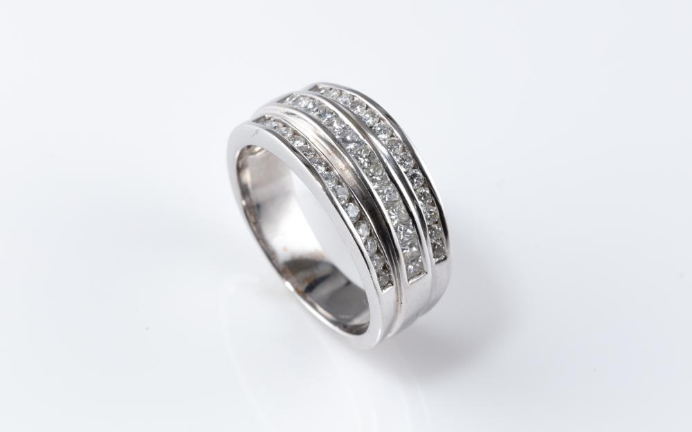 AN 18CT WHITE GOLD DIAMOND RING; set as 3 bands across the top channel set with 1 row of princess cut (13) and 2 rows of round brill...