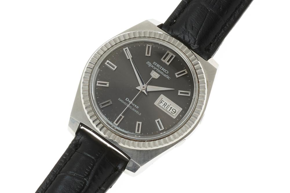 A VINTAGE SEIKO 5 SPORTSMATIC DELUX AUTOMATIC WRISTWATCH; ref. 7619-9040 in stainless steel with cushion form case, round black dial...