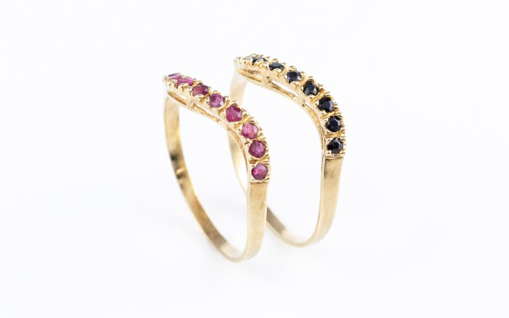 A PAIR OF 14CT GOLD GEMSET STACKING RINGS; wave design set across the top with round cut rubies and sapphires, size P, wt. 2.38g.