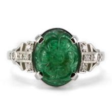 A DECO STYLE 18CT WHITE GOLD EMERALD AND DIAMOND RING; centring on a 10.8 x 7.8 floral carved emerald and 12 round brilliant cut sho...