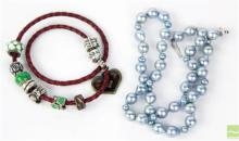PEARL AND CHARM NECKACES; a plaited leather collar attached with assorted charms including Pandora and a cultured silver grey baroqu...