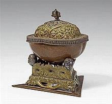 A Tibetan copper kapala with a brass lid and stand with silver details