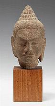 A Bayon-style sandstone head of a deity. Angkor period, 12th/13th century