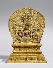 A Tibetan gilt bronze figure of Buddha Shakyamuni on an exremly rare gilt copper repoussé throne with aureole. 15th century