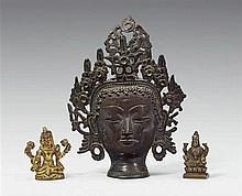 A group of a head of a deity and two miniature figures. Bronze. Tibet. 19th century and later