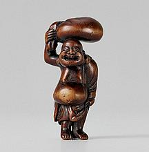 A well worn boxwood netsuke of a pot-bellied Hotei. Late 18th century
