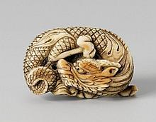 An ivory netsuke of a coiled dragon. Around 1800