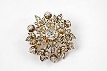 A silver, 14 ct gold and diamond flower brooch.