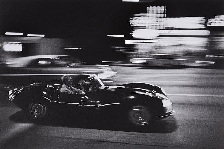 John Dominis, Steve McQueen driving his Jaguar at night, California, 1963