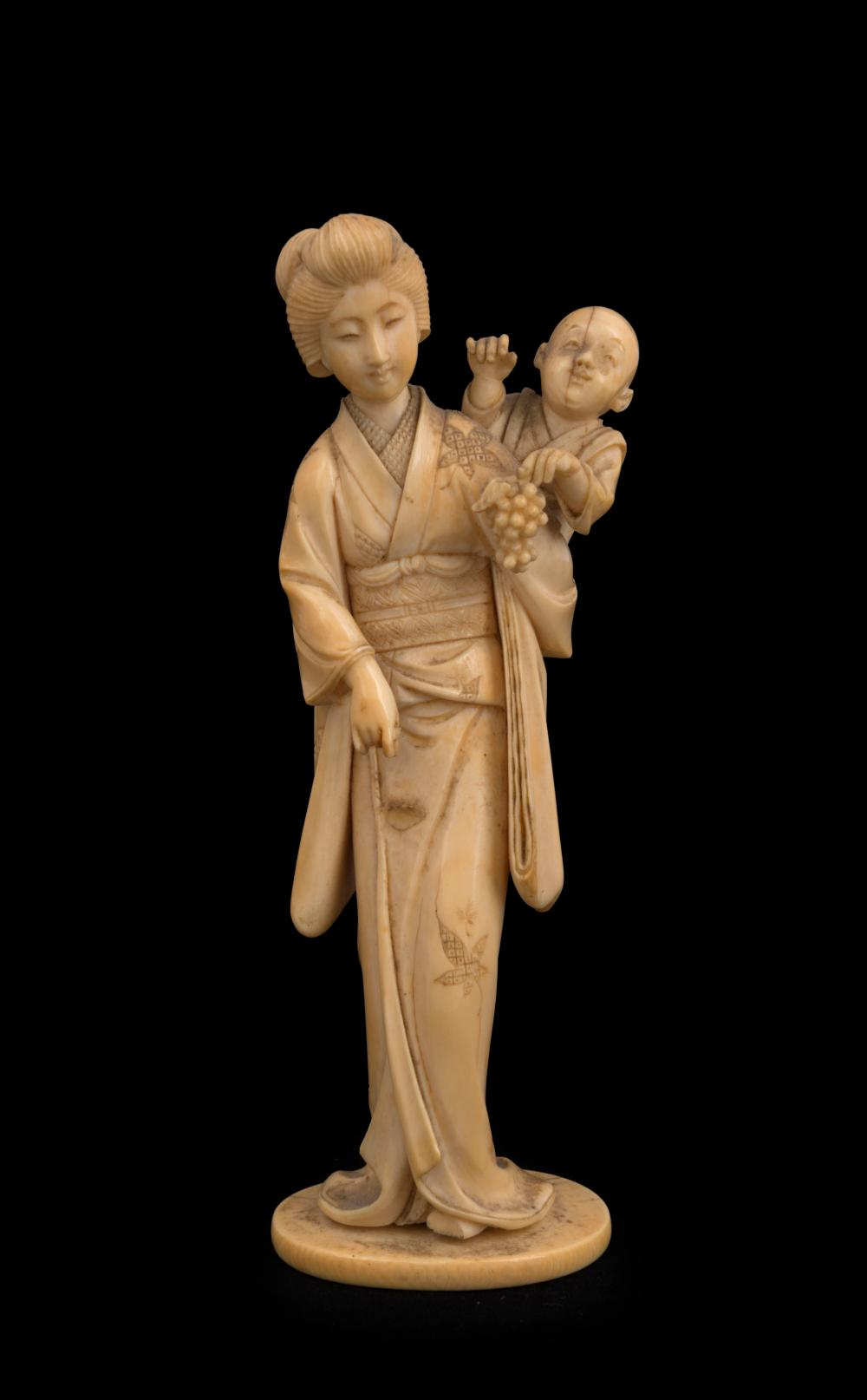 A Japanese carved ivory statue of a lady and child with grapes, Meiji period, 19th century, with two character seal mark to base, 17cm high