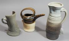 Three pieces contemporary studio ceramics: handled pitchers with grey and brown glazes, two by Tony Winchester (Iowa), one unknown.