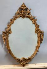 Oval wall mirror with decorative gilt wood frame