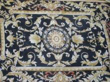 Handwoven Aubusson rug with scrolling design with a black field and ivory border 3' 9