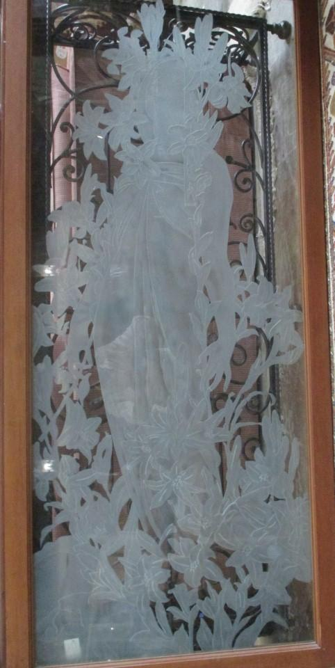 Hanging and framed glass panel with an acid etched female figure of an Art Nouveau woman