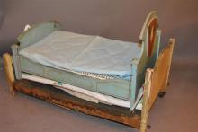 Two vintage wooden doll beds, painted highlights, one on wheel casters, lengths inside: 17 1/2 and 22 inches