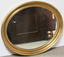 Oval gilt-framed wall mirror.