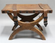 Semi antique leather upholstered stool with large iron tacks and leather straps having hammered iron triangular accents