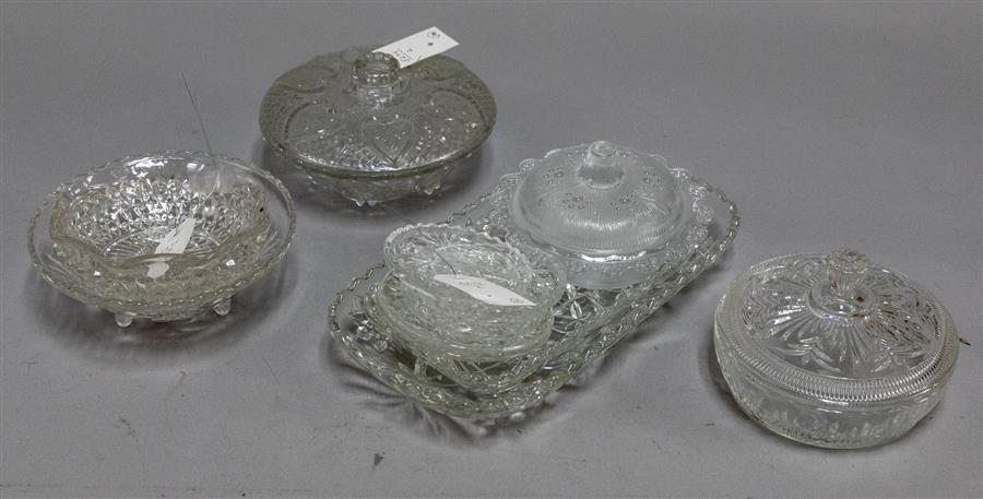 Collection of pressed glass items including bowls, coasters, and serving dishes