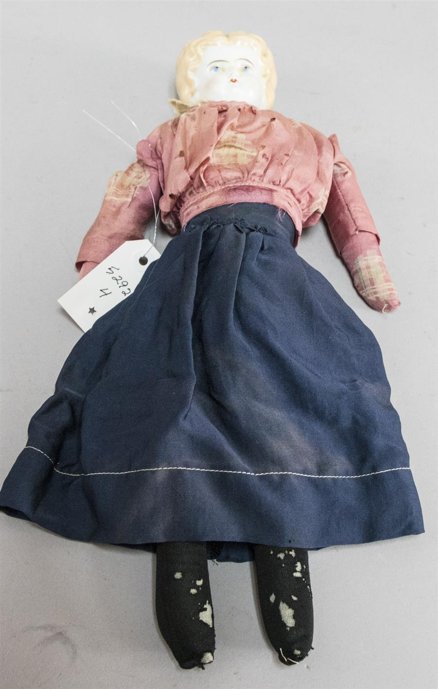 A porcelain head Minerva type doll with cloth body