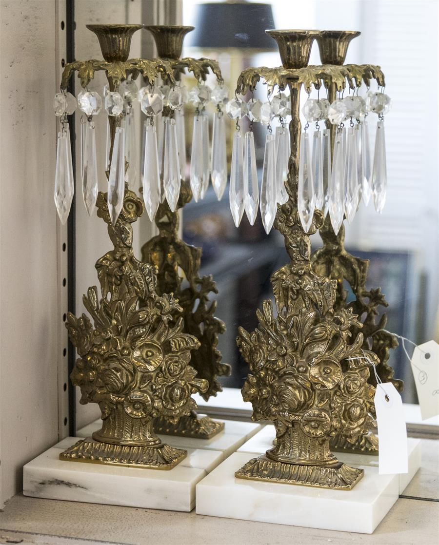 Pair of brass candle holders with floral designs, hanging glass prisms, and marble bases