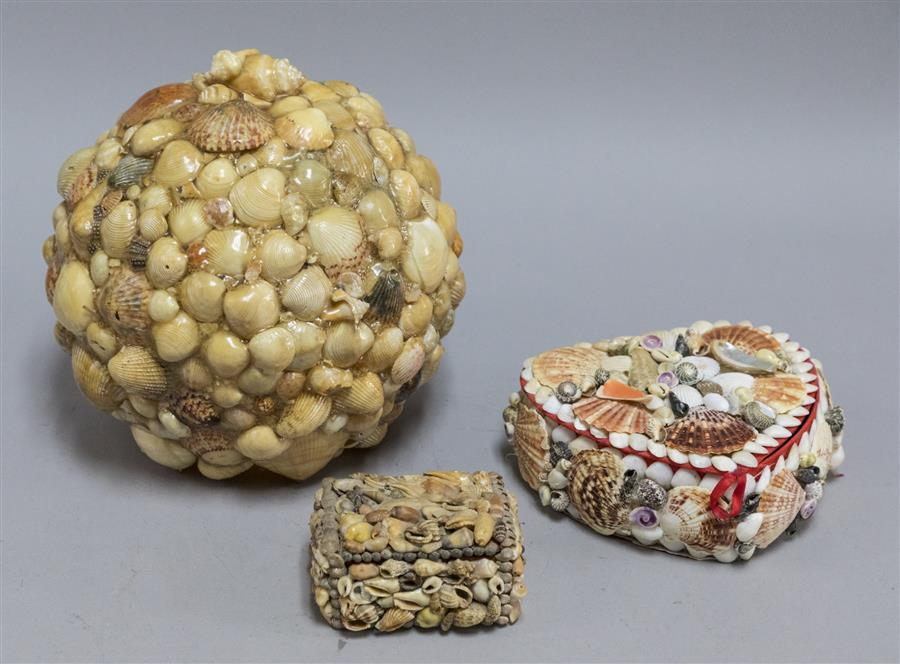 Three decorative pieces covered in sea shells incuding a hinged lidded box, heart shaped box, and glass globe