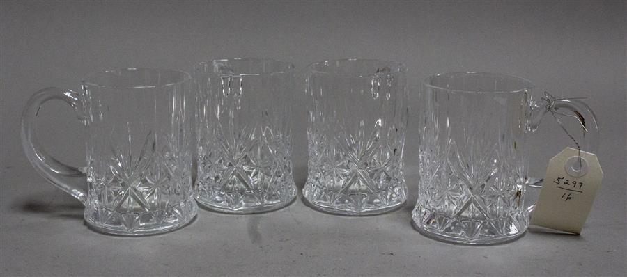 Four pressed glass coffee mugs, an etched glass pitcher with four matching glasses, and a pitcher with six matching glasses having h...