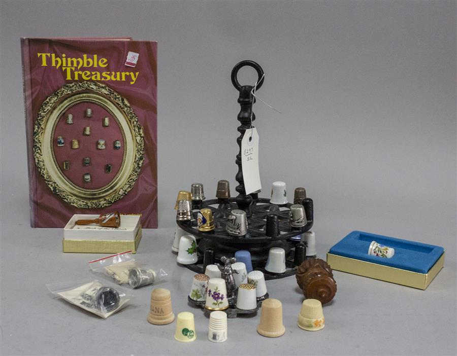 "Collection of vintage thimbles, a book titled, ""Thimble Treasury"", and two display racks"