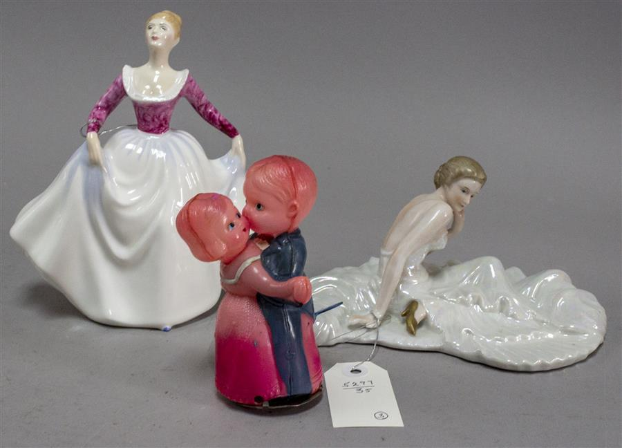 "Porcelain figurine depicting a lady in a full skirt, a Royal Doulton figurine titled ""Lisa"", and a plastic wind-up dancing couple"
