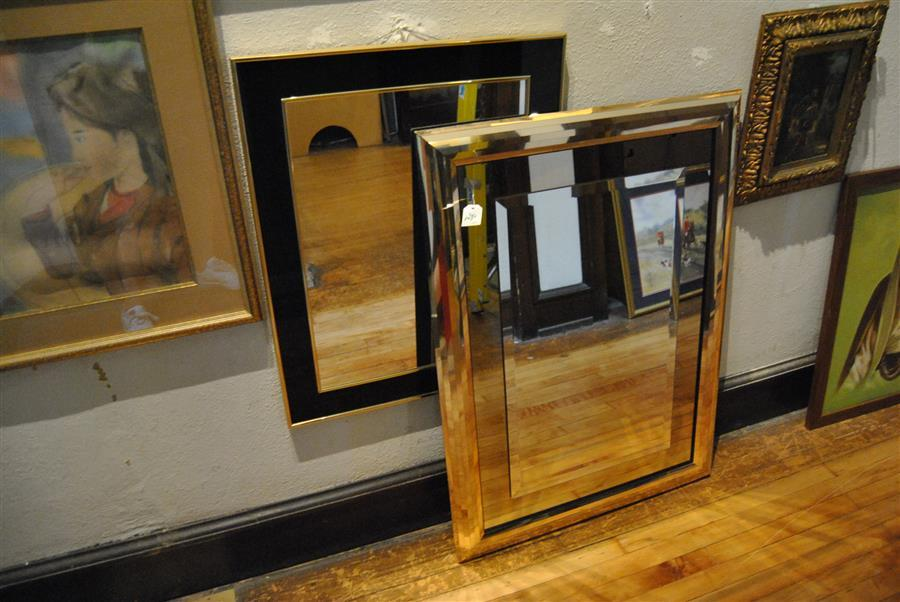 Art deco style mirror with brass frame (41 x 29 1/2 inches) together with a black and gold mirror (30 1/2 x 24 inches)