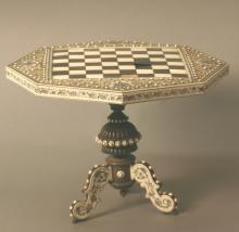 Possibly 19th century Moghul. An ivory inlaid minature chess table. Of Octagonal form on three downswept supports. Some losses the chess squares. 18cm high.27cm wide.