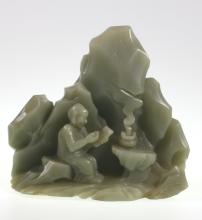 A Rare Chinese Pale Celadon Jade Mountain Boulder. 18th Century Qing Dynasty. Possibly Qianlong period (1736-95). In the form of a seated Luohan writing on a slate next to smoke billowing out from a tripod incense burner. The well-polished Jade of
