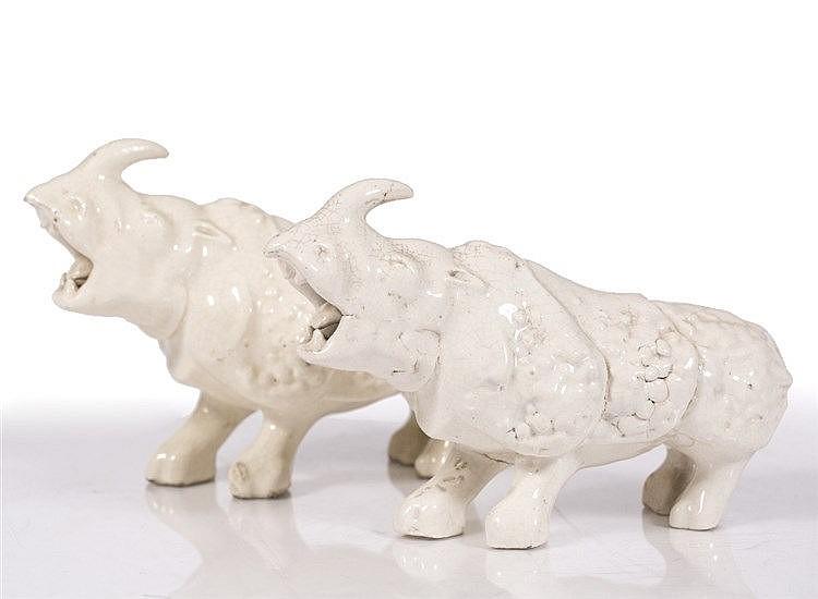 A pair of Chinese white glazed models of rhinoceroses