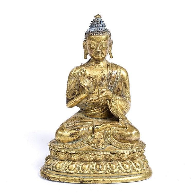 A Tibetan gilt bronze figure of a seated Buddha