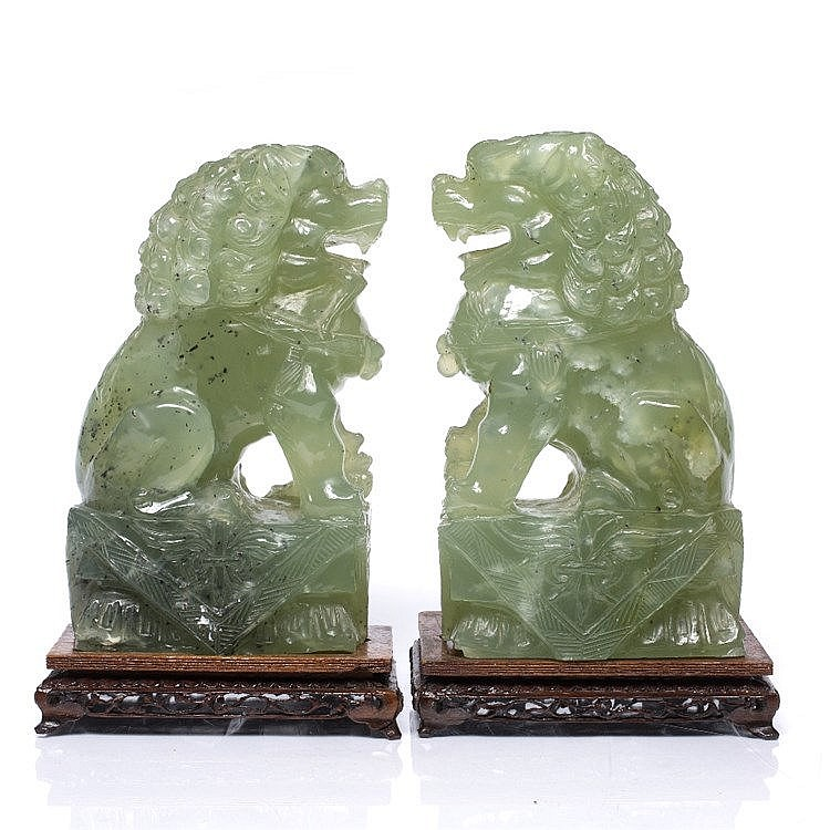 A pair of Chinese carved green hardstone temple dogs